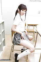 Seated on chair in classroom raising skirt exposing thigh
