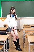 Sitting on desk in classroom playing with skirt hem