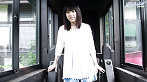 Machiko standing in corridor white top in denim short skirt