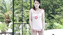 Standing on garden pulling hem of transparent nurse outfit down
