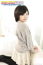 Mei Kadowaki kneeling on couch looking past her shoulder short hair frames her pretty smile wearing short skirt