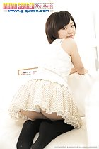 Mei Kadowaki kneeling on couch looking over her shoulder wearing short skirt