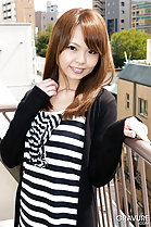 Standing on balcont wearing striped top auburn long hair