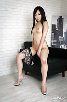 Sitting on arm of chair panties around thigh wearing clear high heels hand resting on thigh pert small tits long hair