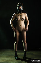 Standing nude with hands on hips bare small breasts pussy hair in boots