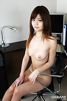 Seated on office chair long hair puffy nipples on her bare breasts hand resting on pantyhose
