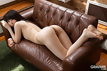 Miku Oguri lying naked on couch looking over her shoulder long hair down her back bare ass raised bare feet dangling over edge of couch