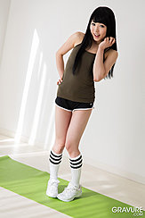 Hand Raised To Her Face Long Hair Wearing Dark Green Top And Shorts In Socks Wearing Trainers