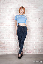 Leaning against wall in crop top wearing jeans