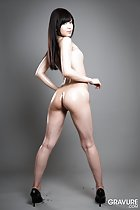 Standing nude looking back long hair nice ass covered in lotion in high heels