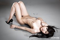 Lying on her back nude knees drawn up hint of pussy hair high heels small tits