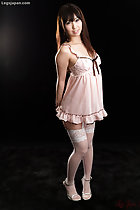 Wearing pink babydoll lingerie in white stockings wearing high heels long hair hands behind her back