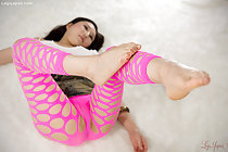 Rubbing her bare foot against her leg in pink pantyhose