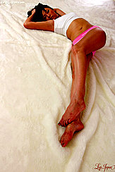 Extending Her Long Legs Bare Feet With Painted Toe Nails Wearing Sleepwear