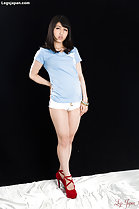 Standing with hand on hip wearing powder blue top in white shorts wearing red high heels