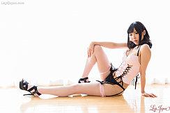 Seated In Lingerie Hand On Raised Knee Wearing Stockings In Black High Heels