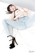 Lying on her back top raised over her breasts wearing jeans legs spread in high heels