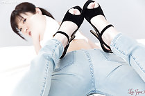 Lying on her front looking over her shoulder in jeans high heels raised