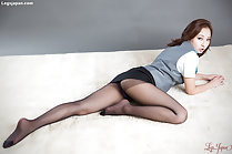 Lying on her front looking over her shoulder short skirt riding up over her pantyhose
